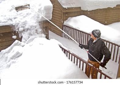 man using a snow rake on garage roof in winter