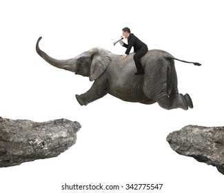 Man with using speaker riding elephant flying over two cliffs, isolated on white background.