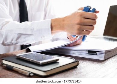 Man using stapler with documents on the table