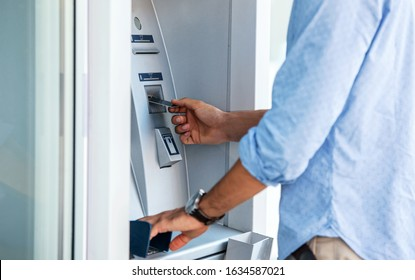 Man using a street ATM machine and withdrawing money, close up photo