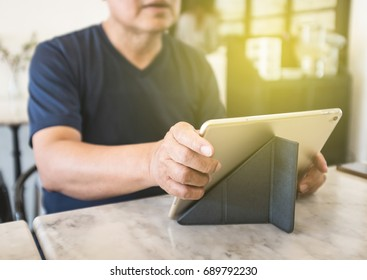 The man using tablet in the coffee shop.