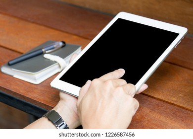 man using tablet computer with blank screen on wooden table, outdoor scene