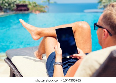 Man using tablet computer on vacation by the pool