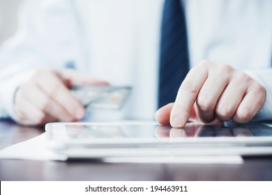 Man Using Tablet and Holding Credit Card.