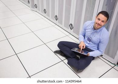 Man using tablet pc sitting beside servers in data center