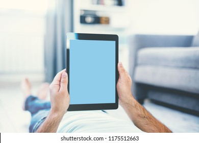 Man Using Tablet PC While Lying on a Floor. View from above. Clipping path included.