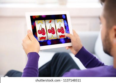 Man using tablet for playing online casino game at home