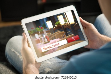 Man using tablet trying to find the perfect restaurant from review website or application. Tavern, cafe or bistro search engine and app online. Rating social media on internet.