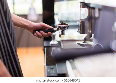 Man is using a tamper to press freshly ground morning coffee into a coffee tablet,Selective focus.