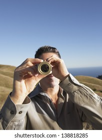 Man using telescope to view distant hills