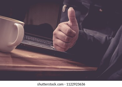 A Man are using Thumbs down to work and sucessful in a working.laptop on a wooden table. Image is Mood tone.