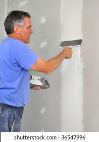 Man using trowel to finish seam between drywall panels