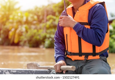 A man using walkie talkie on the boat a while helping the victim of flooding in Thailand