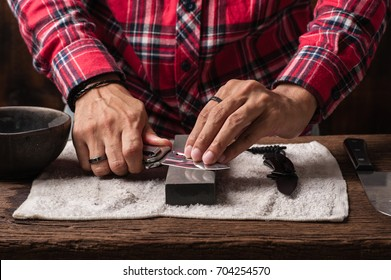 The man using whetstone to sharpening his pocket knife. Pocket knife care and maintenance concept.