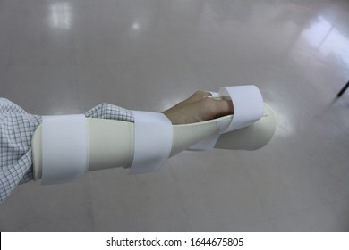 The man using wrist immobiliser after hand injury. Retainer for recovery and release pain in the wrist and hand. Wrist hand splint. Resting hand splint.