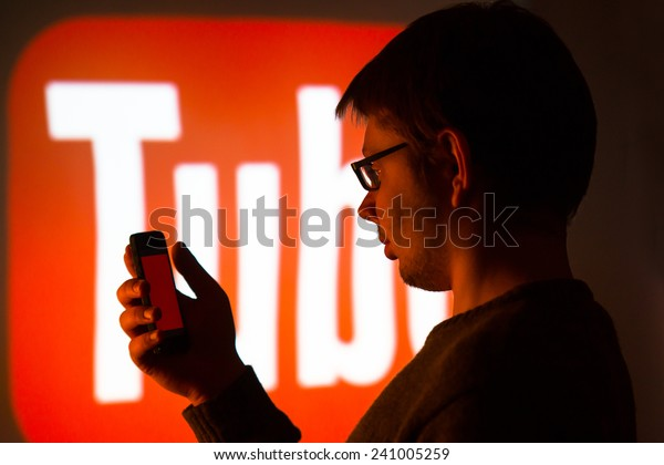 Man using Youtube application on his smartphone, background is an image from the projector - photography from social media meeting in city of Lodz, Poland 07.11. 2014