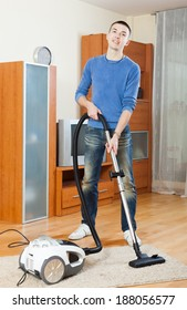 man with vacuum cleaner on parquet floor in living room