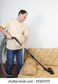 Man vacuums a sofa