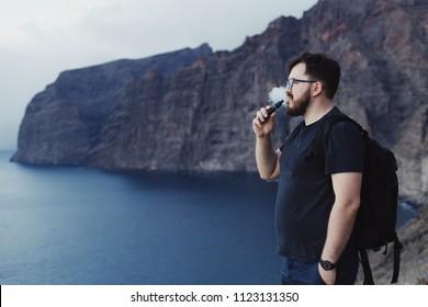Man vaping ecigarette in front of the ocean