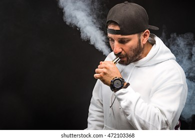 Man vaping an electronic cigarette.Isolated on black background