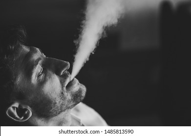 Man with vaping mod exhaling steam at studio. Bearded guy smoking electronic cigarette to quit tobacco. Vape. A cloud of vapor. Alternative nicotine free smoking concept. Black and white photo