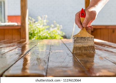 man varnishes a wooden table