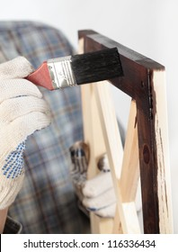 Man varnishing a wooden part of furniture using paintbrush