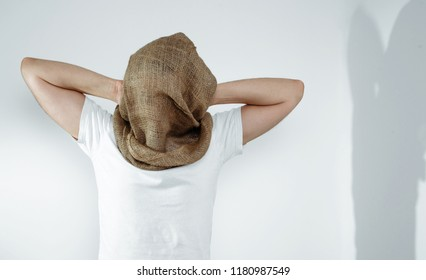 Man with veiled face on a light background. The concept of kidnapping, detention, and crime. No face. The man has a cloth bag on his head. Kidnapping by terrorists.