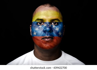 Man with Venezuela flag painted on his face on black background