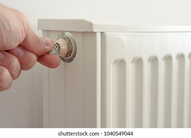 The man venting heating radiator with special key