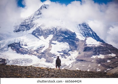 Man versus mountain.  Man staring in awe of a mountain.