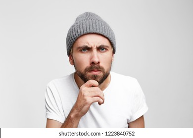 A man very carefully examines something, viewing, and meticulously examines, one hand holding his chin and beard, in the depths of thinking, carefully researching, over white background
