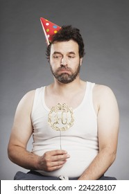 Man in vest, with 40 years wreath and party hat, sad