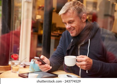 Man Viewed Through Window Of Caf�¢?? Using Mobile Phone