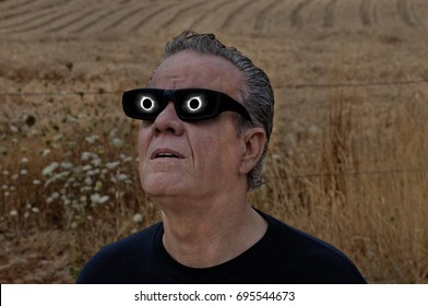 Man viewing full solar eclipse with solar glasses in country field/Man looking at full solar eclipse with eclipse reflecting in lenses