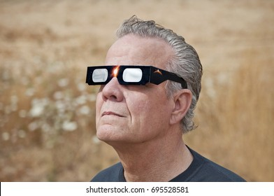 Man viewing solar eclipse with solar glasses in country field /Man looking at the solar eclipse with eclipse glasses