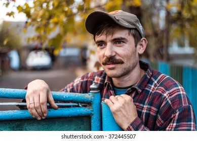 The man in the village in a cap with a mustache