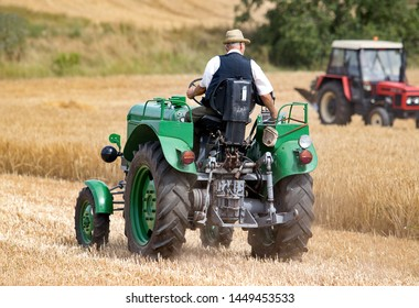 Man from village riding on old tractor on the field