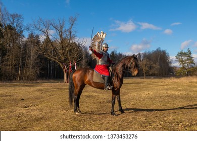 A man in vintage armor with wings a legion of volatile gussars riding a horse against the backdrop of the forest