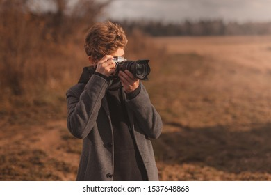 man with a vintage camera in a gray coat and black hoody takes pictures of natural landscape