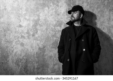 man in vintage cap and coat standing near old wall. black and white photo