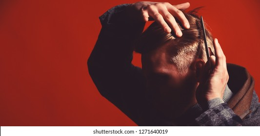 Man in vintage style combing his hair. Barber in suit and scarf with comb on red background. Barbershop and style concept. Stylist makes hairdressers service for himself.