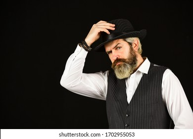 man in vintage style wide brimmed hat. Man with retro Hat. brutal bearded hipster in suit vest. mafia gentlemen club. mature cowboy. detective acknowledgement or greeting. trilby hat. copy space.