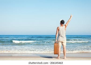 man with vintage suitcase near the sea