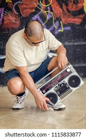 Man with vintage tape boomboxsitting on street at graffiti wall.