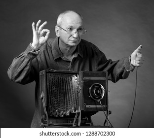 Man with vintage wooden photo camera on a dark background