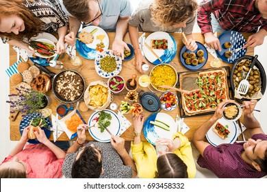 Man in violet shirt eats organic hummus during meeting with vegan friends