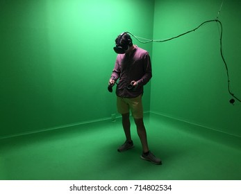 Man in Virtual reality augmented reality arcade - VR experience center. Man interacts with headset that embodies physical spaces or multi-projected environments