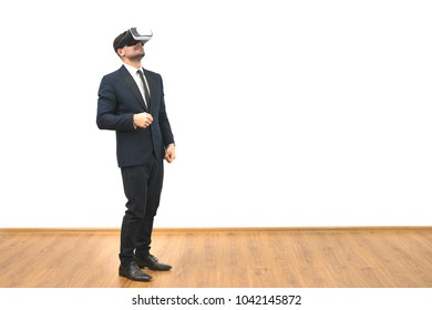 The man in a virtual reality glasses gesturing on the white wall background