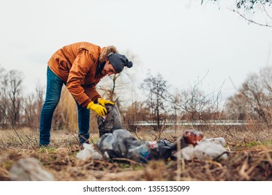 Man volunteer cleaning up the trash in park. Picking up garbage outdoors. Ecology and environment concept